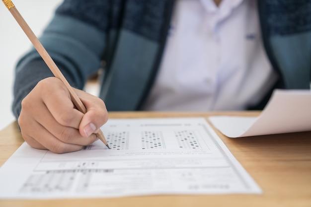 Studente universitario che tiene matita per testare l'esame scrivendo nel foglio delle risposte