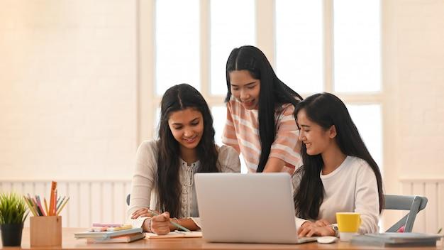 Gli studenti universitari stanno facendo e-learning seduti insieme in salotto.