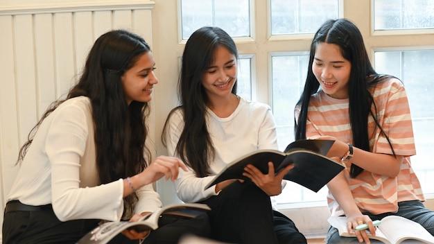 Gli studenti universitari stanno parlando e leggendo una rivista seduti insieme in salotto.