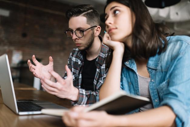Studenti universitari che utilizzano computer portatile, ricerca online, studio in biblioteca. esame fallito uomo arrabbiato. scadenza per il libero professionista