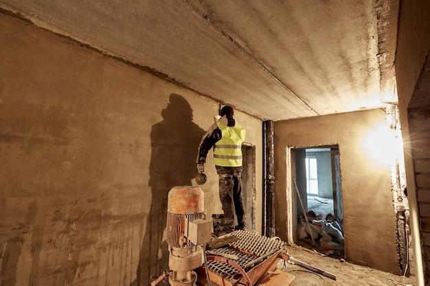 Un costruttore sconosciuto in abiti da lavoro e gilet sta mettendo dello stucco sul muro usando una spatola incompiuta piano di un edificio in costruzione