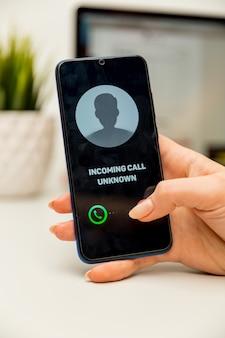 Chiamante sconosciuto. un uomo tiene un telefono in mano e pensa di terminare la chiamata. in arrivo da un numero sconosciuto. incognito o anonimo
