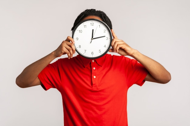 Uomo sconosciuto che nasconde la faccia dietro un grande orologio da parete, gestione del tempo, promemoria della scadenza.