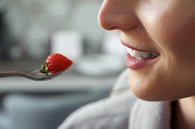 Donna sconosciuta che mangia fragola e sorride, primo piano