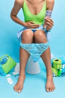 La donna sconosciuta ha problemi di defecazione soffre di mal di stomaco disturbo della digestione tiene le pose di antidolorifici sulla tazza del water isolata sulla parete blu