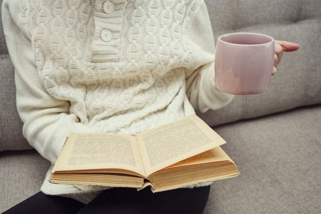 Donna sconosciuta che tiene una tazza di tè e legge un libro.