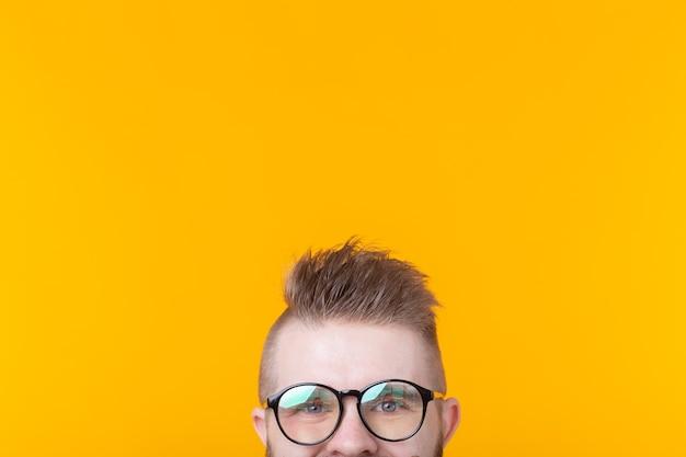 Il giovane studente maschio sconosciuto con i baffi e la barba sta sorridendo mentre levandosi in piedi contro un giallo