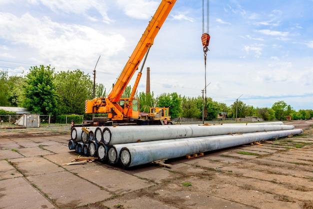 Scarico di pali in calcestruzzo ad alta tensione in cantiere mediante gru di sollevamento. predisposizione per installazione linea ad alta tensione