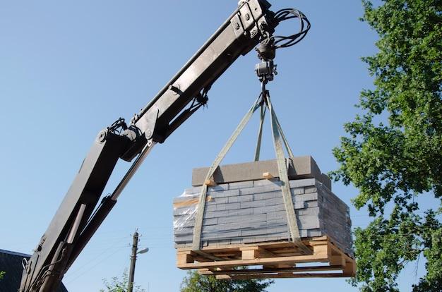 Scarico delle lastre per pavimentazione da un camion, gli operai del manipolatore scaricano la build