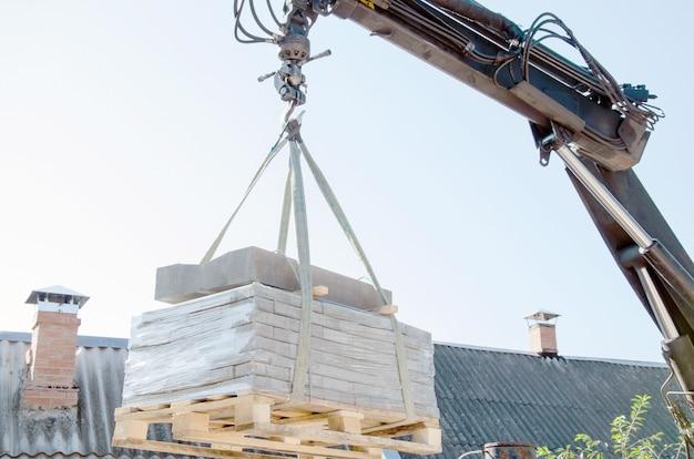 Scarico delle lastre per pavimentazione da un camion, gli uomini scaricano le lastre per pavimentazione utilizzando un manipolatore, gli operai scaricano la costruzione...
