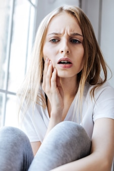Giornata sfortunata. miserabile donna bionda seduta sul davanzale della finestra e con il mal di denti