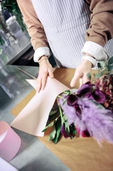 Bouquet straordinario. foto focalizzata su mani maschili che usano carta per ikebana