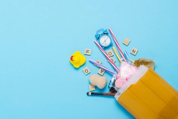 Pacchetto di consegna non imballato con merci di diversi tipi su sfondo blu isolato. pacco di concetto, carico, ordine dalla cina, una selezione di merci, negozio online. vista piana, vista dall'alto.