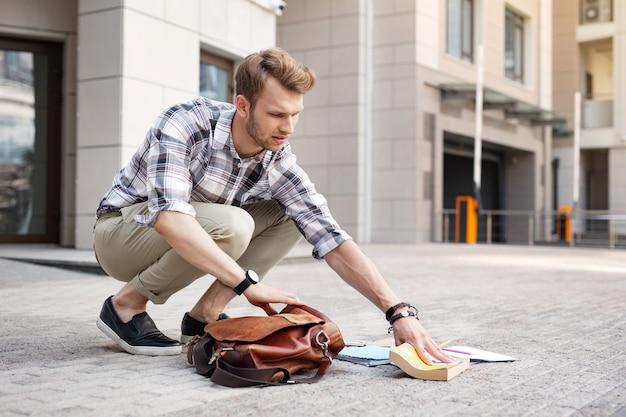 Momenti spiacevoli. uomo infelice depresso che prende un libro da terra mentre vuole rimetterlo nella borsa