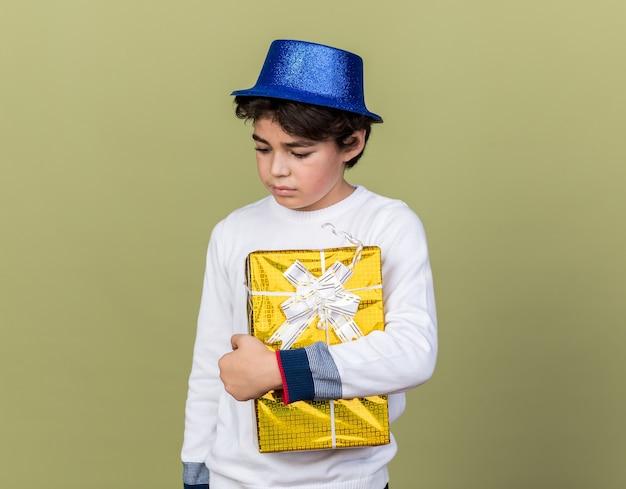 Dispiaciuto guardando in basso il ragazzino che indossa un cappello da festa blu che tiene in mano una scatola regalo