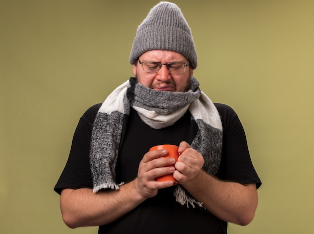 Maschio malato di mezza età scontento che indossa cappello invernale e sciarpa che tiene e guarda una tazza di tè isolata sul muro verde oliva