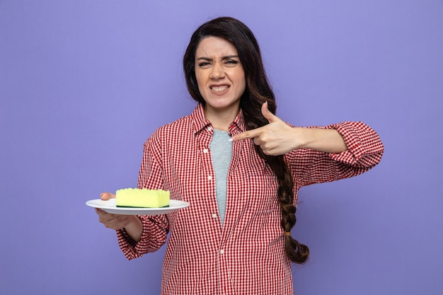 Donna più pulita caucasica scontenta che tiene e indica la spugna sul piatto