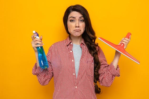 Una donna delle pulizie caucasica piuttosto scontenta che tiene il tergipavimento e il detergente spray e guarda