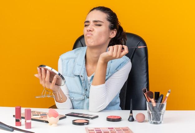 Donna piuttosto caucasica scontenta seduta al tavolo con strumenti per il trucco che tengono pennello per il trucco e specchio isolato sulla parete arancione con spazio di copia