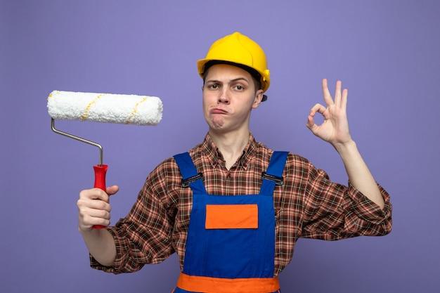 Dispiaciuto che mostra un gesto ok giovane costruttore maschio che indossa una spazzola a rullo con tenuta uniforme
