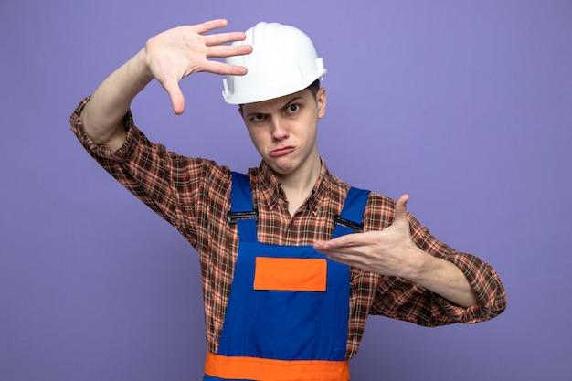 Mostrando scontento il gesto fotografico del giovane costruttore maschio che indossa l'uniforme