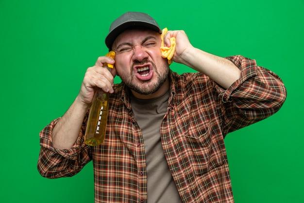 Pulitore slavo scontento che tiene in mano panni per la pulizia e un detergente spray vicino al viso