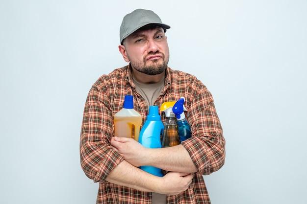 Pulitore slavo scontento che tiene in mano spray e liquidi per la pulizia