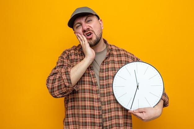Uomo delle pulizie slavo scontento che tiene l'orologio e gli mette la mano sul viso