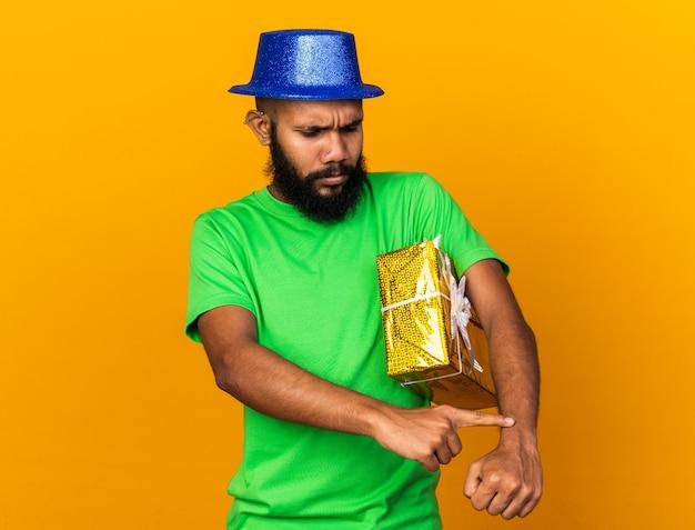 Un giovane afroamericano scontento che indossa un cappello da festa con in mano una scatola regalo che mostra l'orologio da polso