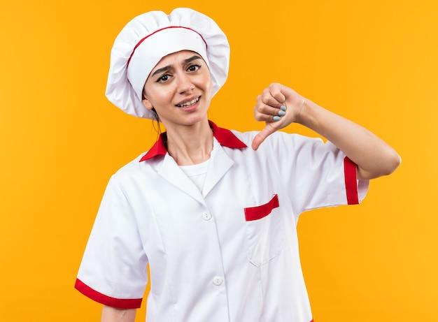 Giovane bella ragazza scontenta in uniforme da chef che mostra pollice in giù