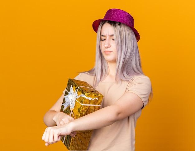 Una giovane bella ragazza scontenta che indossa un cappello da festa che tiene in mano una scatola regalo che mostra il gesto dell'orologio da polso