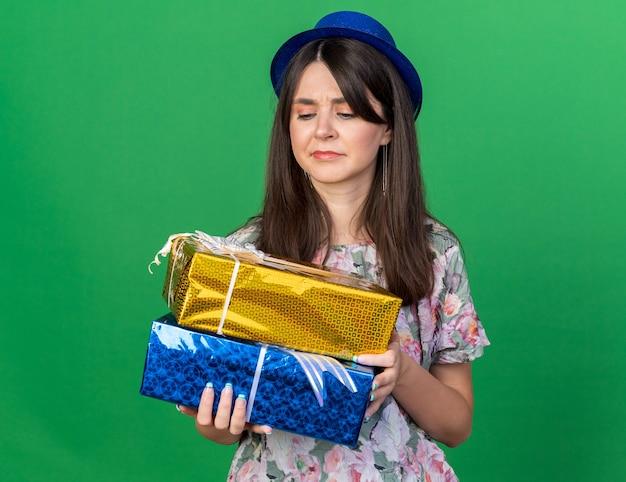Una giovane bella ragazza scontenta che indossa un cappello da festa che tiene in mano e guarda le scatole regalo