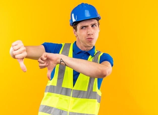 Un giovane costruttore scontento in uniforme che mostra i pollici in giù
