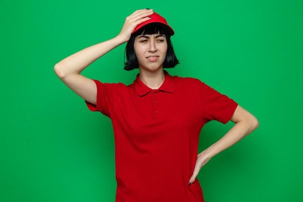 Giovane ragazza delle consegne caucasica scontenta che si mette la mano sulla testa e guarda di lato