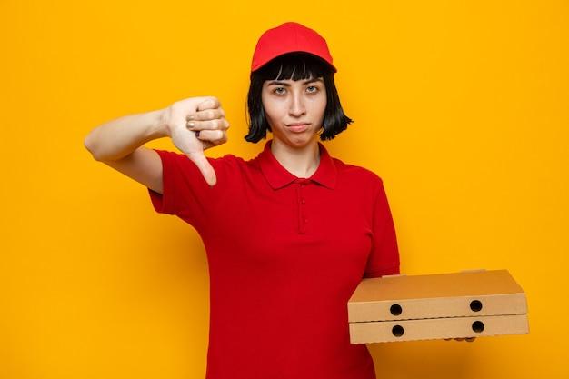 Una giovane donna delle consegne caucasica scontenta che tiene in mano scatole per pizza e fa il pollice verso il basso