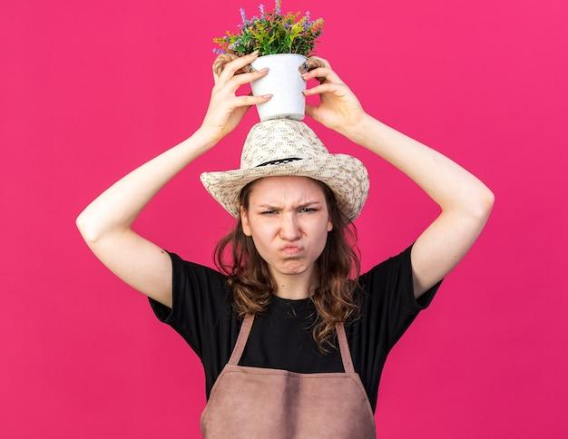 Una giovane giardiniera scontenta che indossa un cappello da giardinaggio che tiene il fiore in un vaso di fiori sulla testa