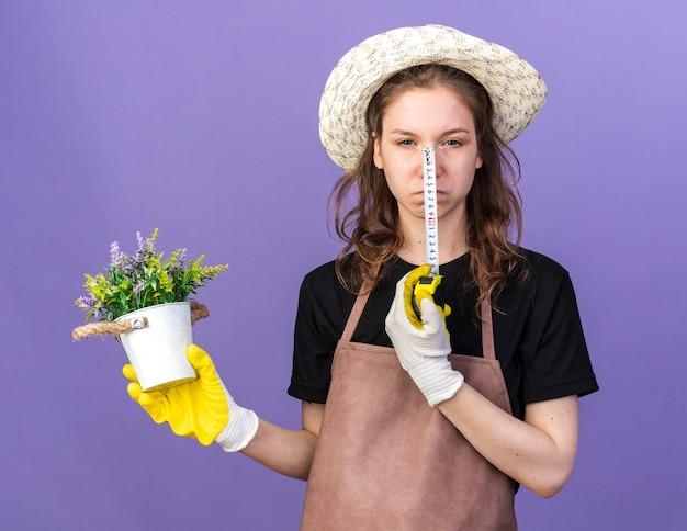 Una giovane giardiniera scontenta che indossa un cappello da giardinaggio con guanti che tengono il fiore in un vaso di fiori con un metro a nastro