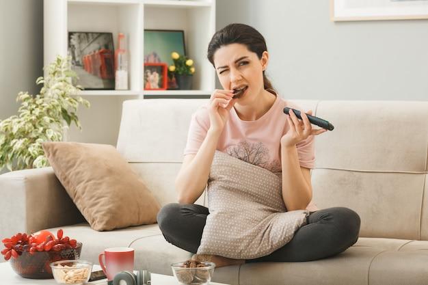 Una ragazza scontenta che tiene in mano il telecomando della tv morde un biscotto seduto sul divano dietro il tavolino da caffè nel soggiorno