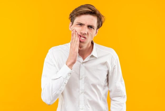 Un bel ragazzo scontento che indossa una camicia bianca che mette la mano sul dente dolorante