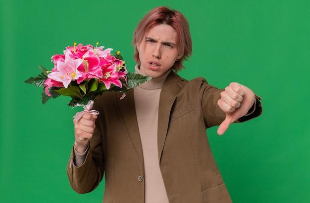 Un bel giovane scontento che tiene in mano un mazzo di fiori e fa il pollice verso il basso