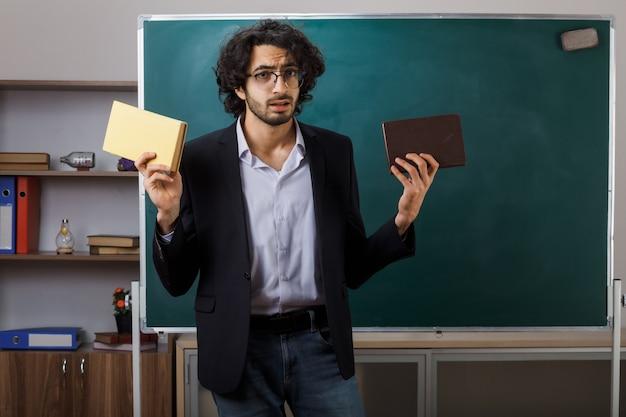 Giovane insegnante maschio scontento che indossa occhiali con libri in piedi davanti alla lavagna in aula