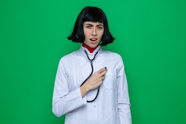 Una giovane ragazza piuttosto caucasica scontenta in uniforme da medico con stetoscopio che ascolta il suo battito cardiaco con lo stetoscopio