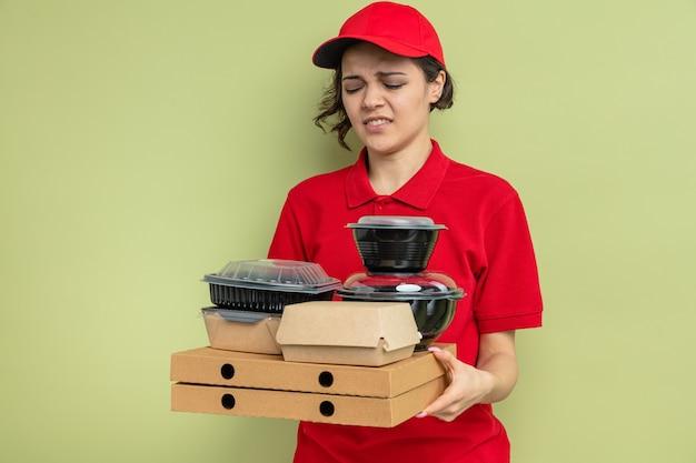 Una giovane e graziosa donna di consegna scontenta che tiene e guarda i contenitori per alimenti con imballaggi su scatole per pizza
