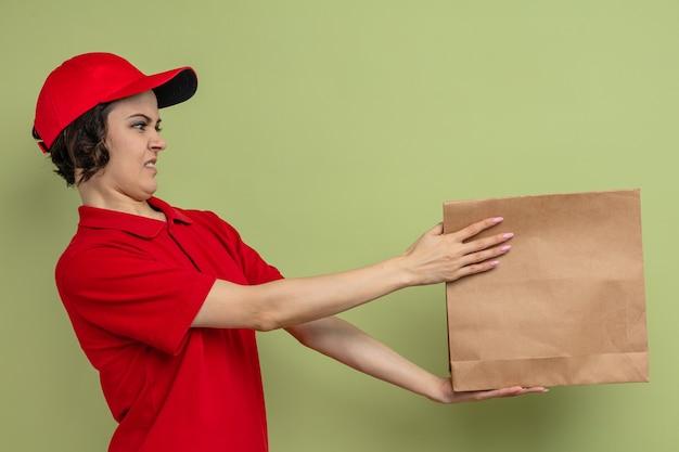 Giovane e graziosa donna delle consegne scontenta che tiene in mano e guarda il sacchetto di carta per alimenti