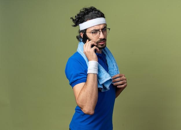Il giovane sportivo scontento che indossa la fascia con il braccialetto e l'asciugamano sulla spalla parla al telefono