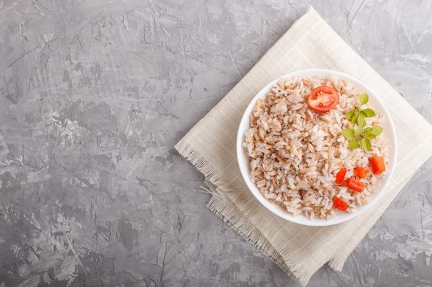 Porridge di riso non lucidato in ciotola bianca su una priorità bassa concreta grigia. vista dall'alto, copia spazio.