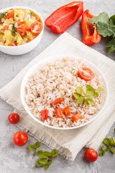 Porridge di riso non lucidato con verdure stufate e origano in ciotola bianca su uno sfondo grigio cemento
