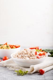 Porridge di riso non lucidato con verdure in umido e origano in ciotola bianca su una superficie di cemento grigia. vista laterale, copia spazio.