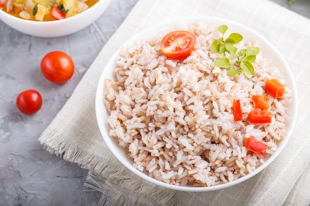 Porridge di riso non lucidato con verdure in umido e origano in ciotola bianca. vista dall'alto, da vicino.