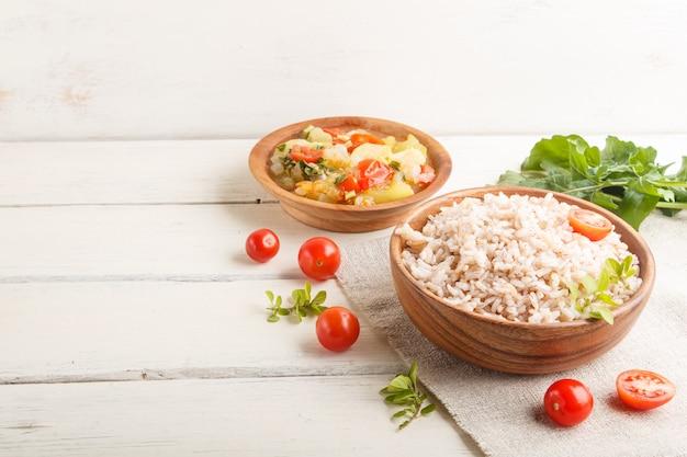 Porridge di riso non lucidato con verdure stufate e origano in ciotola di legno su un fondo di legno bianco